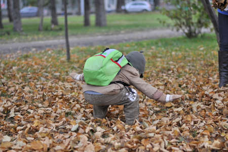 packsack: little boy raking leaves in autumn park Stock Photo