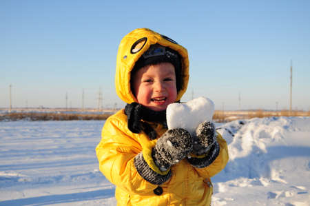 Smiling boy with snow heart photo