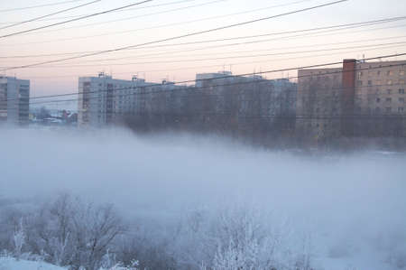 morn: Winter city at the fog in Siberia