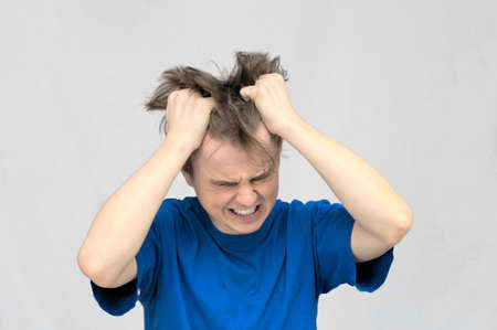 White caucasian man ripping his hair with two hands