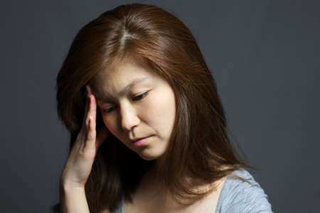 Asian woman with headache , dark background photo