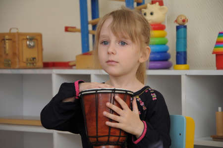 drumming: White caucasian Cute girl drumming in kindergarten