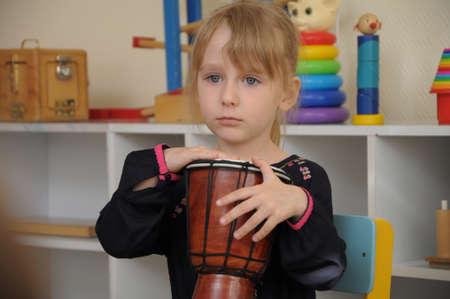 drumming: White caucasian Cute girl drumming in kindergarten