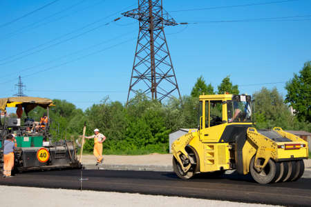 pave: Workers waiting while rolling machinery pave asphalt