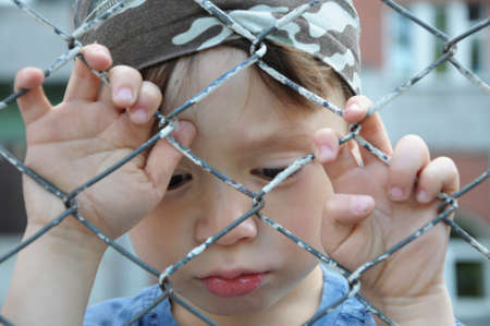 Caucasian sadly boy looking through the bars outdoor