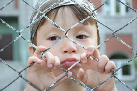 Caucasian boy looking unhappy through the bars outdoor