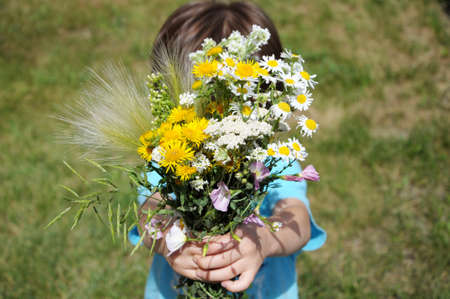 gifting: Boy giving summer bouquet of flowers