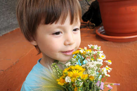 donative: Boy enjoying summer bouquet of wildflowers with smile