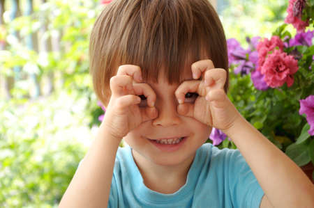 Boy playing and making glasses with hands photo