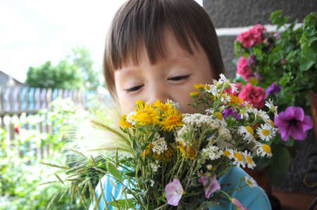 Boy smelling summer bouquet of wildflowers outdoor photo