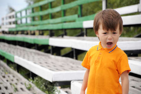 grouch: boy screaming in discontent, outdoor, summer time Stock Photo