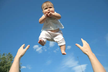 tossing: Daddy tossing up a baby, sky background