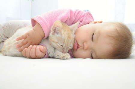 아기와 흰색 시트에 함께 잠자는 고양이