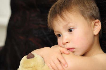 Pensive boy on dark coach with Teddy bear photo
