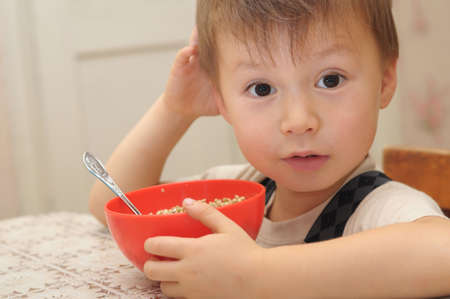 suppertime: Four year old boy at lunch with buckwheat in red bowl