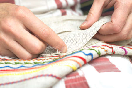 Woman hands sewing with needle and thread photo