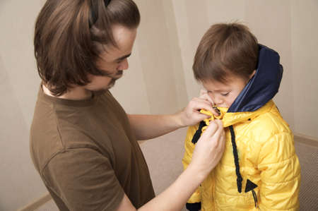 'rig out': father clothing his son to the street in a warm jacket Stock Photo