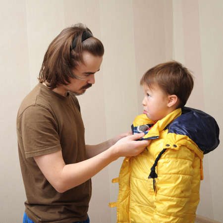'rig out': father dressing his son to the street in a warm jacket Stock Photo