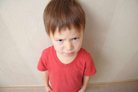 malign: resentful angry cute boy looking from below Stock Photo