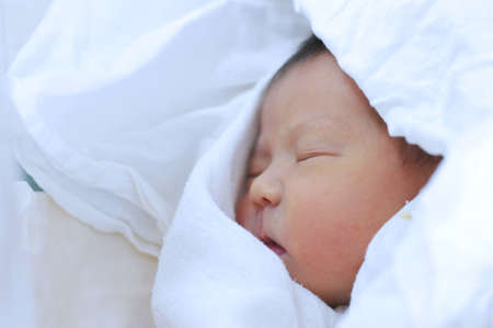 one sheet: Newborn baby on one day life covered in sheet Stock Photo