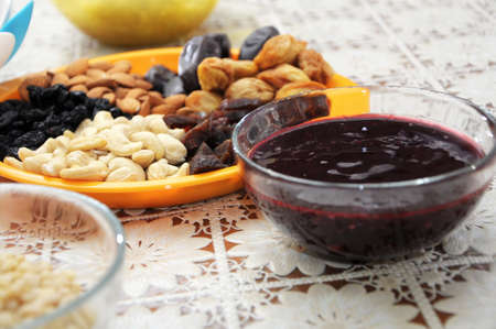 convivial: dried fruits, nuts and currant jam on table