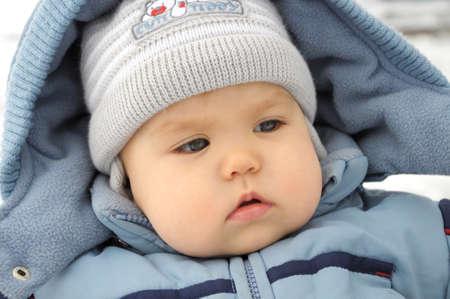 overall: Peque�o retrato del beb� cauc�sico en invierno azul global Foto de archivo