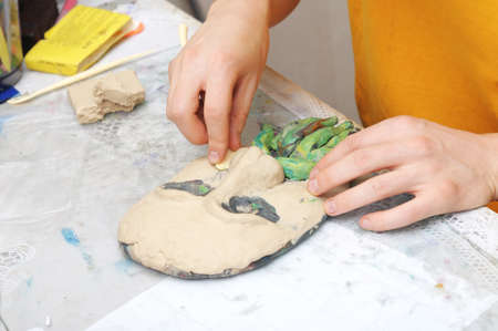 visard: Man hands sculpting plasticine form of face
