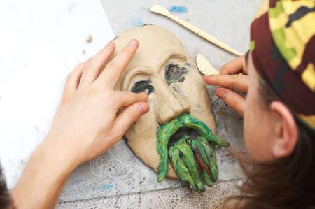 콧수염과 얼굴의 plasticine 양식을 조각하는 사람