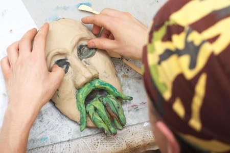 visard: Man sculpting plasticine form of face with moustache Stock Photo