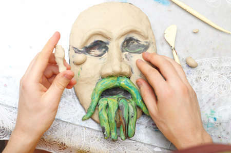 visard: Man hands sculpting plasticine form of face with moustache