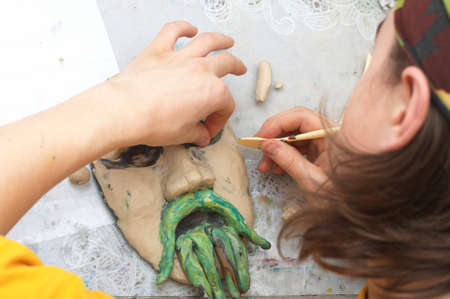visard: Man sculpting craft with plasticine the form of face with moustache Stock Photo