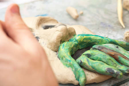 visard: Hands sculpting craft with plasticine the form of face with moustache Stock Photo