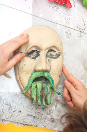 adeptness: Hands sculpting craft with plasticine the form of face with moustache Stock Photo