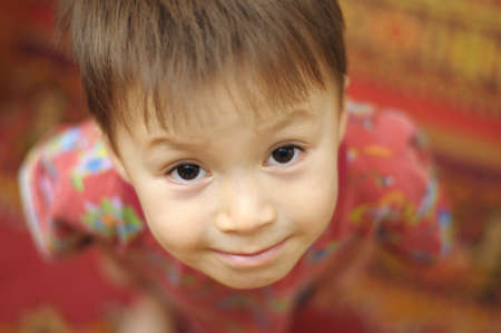 diminutive: Caucasian boy portrait from above on red background
