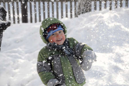 beatitude: Boy in warm clothes behind falling snow in winter