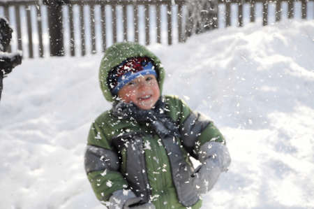 felicity: Smiling boy behind falling snow in winter