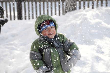 beatitude: Smiling boy behind falling snow in winter