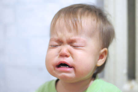 snotty: Very emotionally crying weeping baby face portrait Stock Photo
