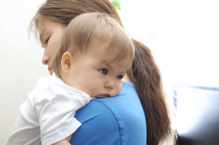 appease: Baby laying head on mothers arm at home