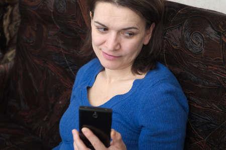 stylishness: portrait of sitting woman using a smartphone Stock Photo