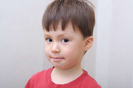 artful: Caucasian boy face portrait looking sly and artful Stock Photo