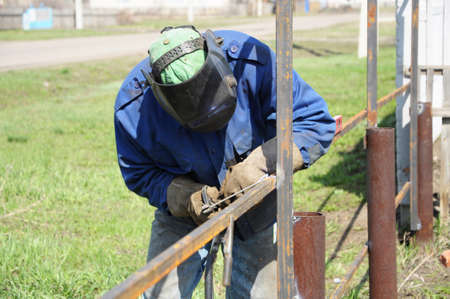 erecting: welder outdoor working and soldering iron with mask