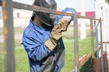 hammering: welder outdoor working and hammering iron with mask