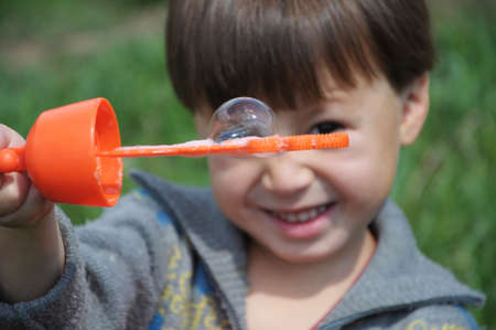 inflate: Soap bubble on stick holding by kid on summer Stock Photo