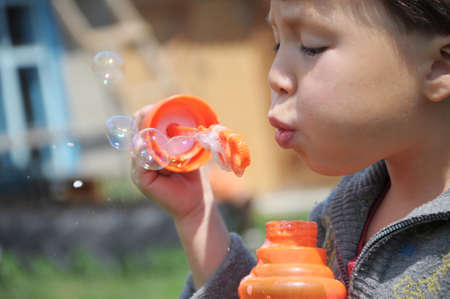 kiddy: Boy blowing the soap bubbles at summer outside Stock Photo