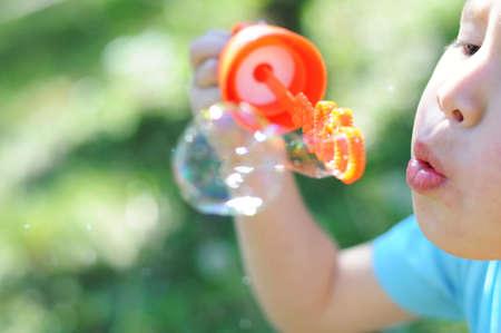 여름에 밖에서 비누 거품을 만드는 소년