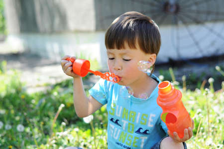 kiddy: Caucasian boy inflating the soap bubbles outside