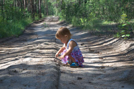 babies playing: Baby girl on the field road playing in the forest