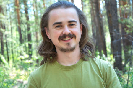 long hairs: Man portrait smiling in the forest