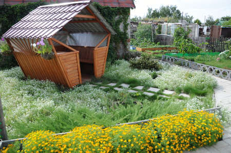 quietude: garden house in the summer surrounded flowers